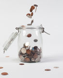 Jar with change falling isolated Stock Images