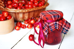 Jar with cherries on the white wooden table Royalty Free Stock Photo