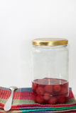 Jar of cherry compote on the kitchen tablecloth Royalty Free Stock Photography