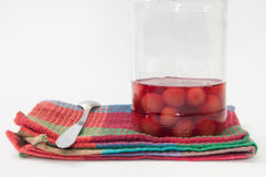 Jar of cherry compote on the kitchen tablecloth Royalty Free Stock Photo