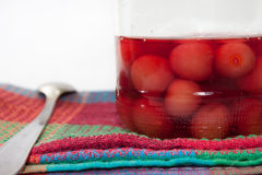 Jar of cherry compote on the kitchen tablecloth Stock Photos