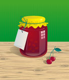 Jar of cherry jam. With label on wooden table Royalty Free Stock Images