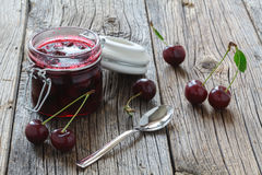 Jar of cherry jam and some cherries on board stock photo