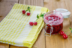Jar of cherry jam and some cherries on the napkin. Jar of cherry jam and some cherries on the yellow napkin. Wooden table background Stock Image