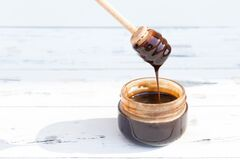 A jar of chocolate dessert, honey or cosmetic masque on white wooden background. Free copy space.