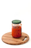 A jar of chutney on a kitchen wooden board Royalty Free Stock Images
