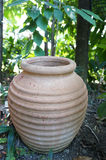 Jar of clay in the garden. Jar made of clay is placed on the ground in the garden Royalty Free Stock Images