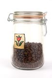 A jar with coffee beans. A glass jar with coffee beans (filled up to a half Royalty Free Stock Photo