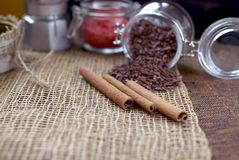 A jar with coffee beans, cinnamon sticks, a sweet chocolate ingredient in a jar,. A tea kettle Stock Images