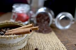 A jar with coffee beans, cinnamon sticks, a sweet chocolate ingredient in a jar,. A tea kettle Royalty Free Stock Photo