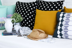 Jar, coffee cup and books with colorful pillows in background Royalty Free Stock Photography