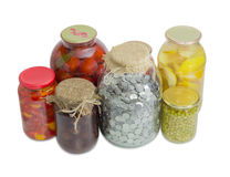 Jar with coins among home canned fruit and canned vegetable Royalty Free Stock Photos