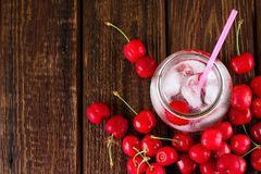 Jar with cold drink with many cherries around Royalty Free Stock Photography
