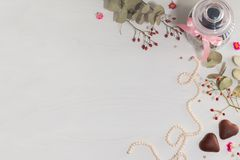 Jar for cookies, pearl necklace, two cookies in form of heart and branches of evkalipt on light background. Royalty Free Stock Photo