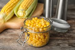 Jar with corn kernels. On wooden table stock photos