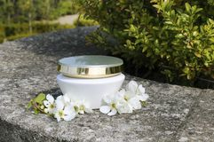 Jar of cosmetic cream and flower stock photo