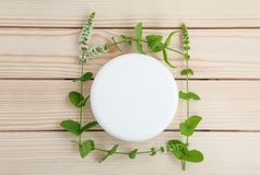 Jar of cream with sprigs of fresh mint on a wooden background. Top view. Jar of cosmetic skin care cream next to a sprig of fresh mint on a wooden background royalty free stock photography