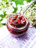Jar of cranberry jam, selective focus. Preserved food. Morning still life. Food for breakfast or snack. Jam with bread Royalty Free Stock Images