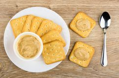 Jar of cream cheese, teaspoon and crackers smeared cream cheese. On wooden table. Top view Royalty Free Stock Photos