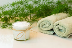 Jar with cream, towels and greens on bathroom countertop Royalty Free Stock Images