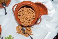 Jar with crispy almond flesh seeds on a table. Royalty Free Stock Photos