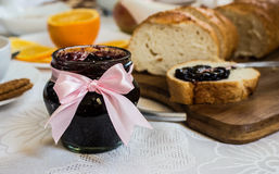Jar of currant jam on table with loaf of bread Stock Photography