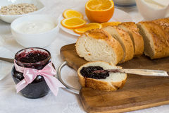 Jar of currant jam on table with loaf of bread Stock Image