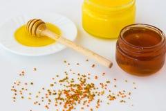 Jar with a dark honey. Dipper honey with a light honey. Pollen o Stock Images