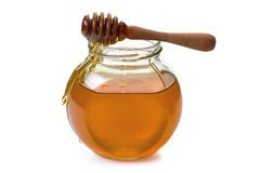 Jar with dripper an flowing honey on white Stock Photos