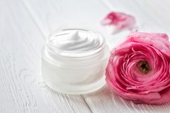 Jar with face cream and pink ranunculus flower on a on a wooden surface. The place for the text. Close up. stock images