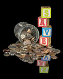 Jar filled with change spilled with the word SAVE Royalty Free Stock Photos