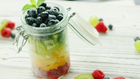 Jar filled with colorful fruit. From above shot of jar filled with colorful mix of sweet fruit and berry mix and served on table stock footage