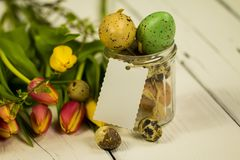 Jar filled with easter eggs and a badge with free text space. Bouquet of different colored tulips, a jar full of quail eggs and colored Easter eggs with empty Stock Image