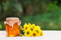 A jar of flower honey and yellow flowers. Fresh homemade honey. Copy space Stock Photo