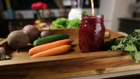 Jar of fresh beet smoothie with vegetables in tray stock video footage