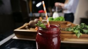 Jar of fresh beetroot smoothie with striped straw. Closeup mason jar of healthy fresh beetroot smothie with striped raw and mint leaves for decoration over stock video footage