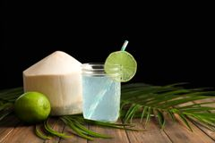 Jar with fresh coconut water and lime. On table against black background Stock Images