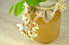 Jar of fresh delicious honey with acacia flowers Royalty Free Stock Image