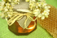 Jar of fresh delicious honey with honeycomb and acacia flowers Royalty Free Stock Images