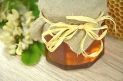 Jar of fresh delicious honey with honeycomb and acacia flowers Royalty Free Stock Image
