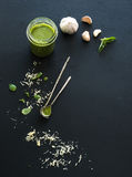 Jar of fresh home made pesto with ingredients for Stock Image