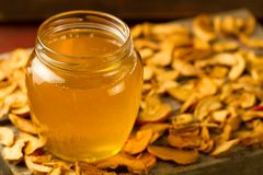 Jar of fresh honey with dried apples on wooden background Royalty Free Stock Image
