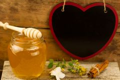 Jar of fresh honey with drizzler, cinnamon, flowers on wooden background Royalty Free Stock Images