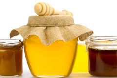 Jar of fresh honey with drizzler and flowers isolated on white background Royalty Free Stock Photo