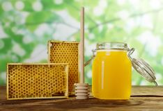 Jar of fresh honey, frames with bee honeycombs and spoon on wooden surface. Jar of fresh honey, frames with bee honeycombs and honey stirrer, on wooden surface Royalty Free Stock Photos