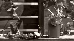 Jar of fresh juice. Cranberries fresh fruit in a huge glass on a wooden table outdoors in the yard stock footage