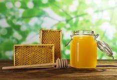 Jar of fresh may honey, bee honeycombs and spindle, on table. Jar of fresh may honey, bee honeycombs and spindle, on wooden table Royalty Free Stock Photos