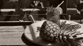 Jar of fresh pineapple juice. Cranberries and pineapple fresh fruit in a huge glass on a wooden table outdoors in the yard stock video