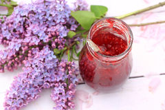 A jar of fresh raspberry jam on light rustic background in the garden, selective focus Royalty Free Stock Photo