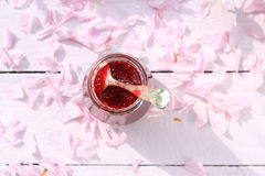 A jar of fresh raspberry jam on light rustic table covered with cherry flowers, romantic breakfast background, close up, in the ga. A jar of fresh raspberry jam Royalty Free Stock Image